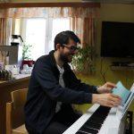Chorleiter sitzt am Klavier