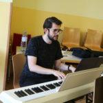 Chorleiter sitzt am Klavier und spielt darauf